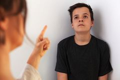 Young teenager boy bored by the constant lecturing and confrontation with his mother stock photos