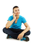 A young teenager boy on the cell phone looking up. Isolated on a white background Stock Photos