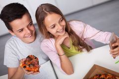 Young teenager boy and girl study together - eating pizza stock images