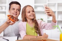 Young teenager boy and girl taking a selfie - eating pizza stock photos