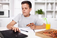 Young teenager boy working on a project having a bite of pizza royalty free stock photos