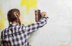 Young teenager brunette girl with long hair applying white putty on a wall and smearing by putty knife in a room of renovating hou. Se in daytime stock photo