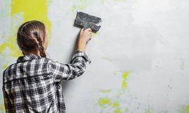 Young teenager brunette girl with long hair applying white putty on a wall and smearing by putty knife in a room of renovating hou. Se in daytime royalty free stock photos