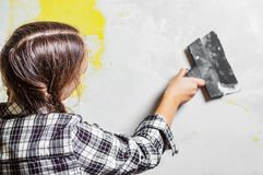 Young teenager brunette girl with long hair applying white putty on a wall and smearing by putty knife in a room of renovating hou. Se in daytime royalty free stock photo