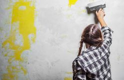 Young teenager brunette girl with long hair applying white putty on a wall and smearing by putty knife in a room of renovating hou. Se in daytime royalty free stock images