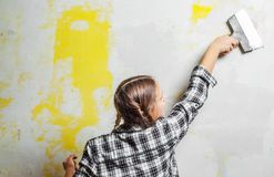 Young teenager brunette girl with long hair applying white putty on a wall and smearing by putty knife in a room of renovating hou. Se in daytime stock images