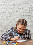 Young teenager brunette girl with long hair drawing with brush at a table on gray wall background with copy space. royalty free stock image