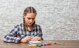 Young teenager brunette girl with long hair drawing with brush at a table on gray wall background with copy space. royalty free stock photo
