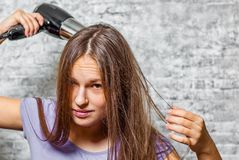 Young teenager brunette girl with long hair dries hair with electrical hair dryer on gray wall background stock photos