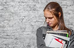 Young teenager brunette girl with long hair holding books and note books wearing backpack on gray wall background stock images
