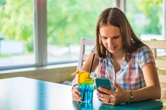 Young teenager brunette girl with long hair sitting indoor in urban cafe, drink a blue lemonade cocktail and use her smartphone stock photos