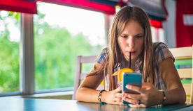 Young teenager brunette girl with long hair sitting indoor in urban cafe, drink a blue lemonade cocktail and use her smartphone royalty free stock photography