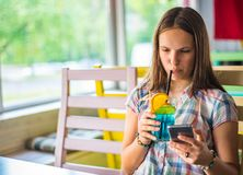 Young teenager brunette girl with long hair sitting indoor in urban cafe, drink a blue lemonade cocktail and use her smartphone stock photography