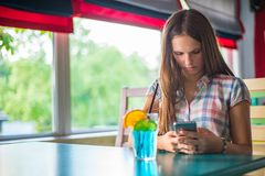 Young teenager brunette girl with long hair sitting indoor in urban cafe, drink a blue lemonade cocktail and use her smartphone stock images