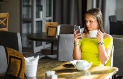 Young teenager brunette girl with long hair sitting indoor in urban cafe and use her smartphone royalty free stock photo