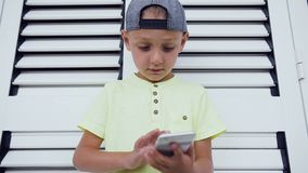 Young teenager in cap playing game on smartphone, isolated on white door background. Child playing with smartphone. Technology. Close-up of young boy who write stock video footage