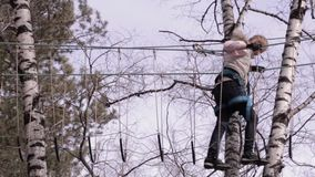 Young teenager climber walks by pendant log bridge on high ropes course in extreme park stock video footage