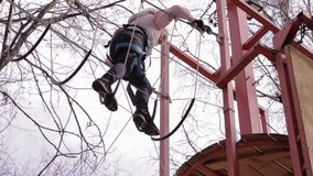 Young teenager climber walks by pendant log bridge on high ropes course in extreme park stock footage