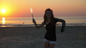 Young teenager female dancing in the twilight on a beach with a firework candle stock footage