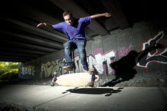 Young teenager flipping his longboard Stock Photography