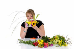 Young teenager girl arranging. Flowers on reflective surface, white background, studio shot Royalty Free Stock Photography