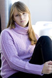 Young teenager girl with depressed expression. Young teenager girl with blond hair sitting in a strong sad depressed expression Royalty Free Stock Photos