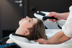 Young teenager girl in hairdressing salon washing hair by male hairdresser's hands. Royalty Free Stock Images