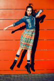 Young teenager girl having fun, posing and jumping near red wall background in skirt and jeans jacket on the sunset. Royalty Free Stock Photo