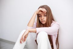 Young teenager girl having a heartache - sitting on the floor by stock image