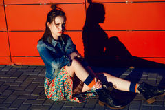Young teenager girl posing and sitting near urban red wall background in skirt and jeans jacket on the sunset. Stock Image