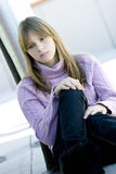 Young teenager girl with sad depressed expression. Young teenager girl with blond hair and bangs sitting with her knee bent in sad depressed expression royalty free stock photo