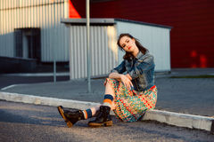 Young teenager girl sitting on the road outside near urban red wall background in skirt and jeans jacket on the sunset. Stock Images