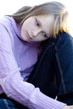 Young teenager girl sitting with sad expression. Young teenager girl sitting with her knee bent in sad depressed expression Royalty Free Stock Photography