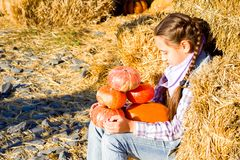 Young teenager girl sitting on straw with pumkins on farm market. Family celebrating thanksgiving or halloween. royalty free stock image
