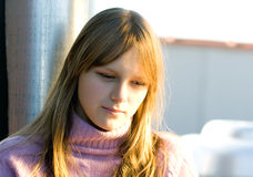 Young teenager girl with thinking expression. Young teenager girl with blond hair looking down with thinking expression on her face stock image