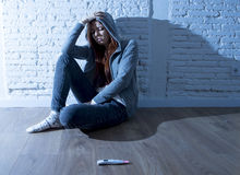 Young teenager girl or young woman in shock scared after positive pregnancy test. Young red hair teenager girl or young woman in shock and overwhelmed after stock photos