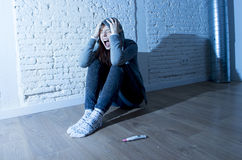 Young teenager girl or young woman in shock scared after positive pregnancy test. Young red hair teenager girl or young woman screaming in shock and overwhelmed stock image