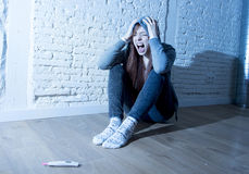 Young teenager girl or young woman in shock scared after positive pregnancy test Royalty Free Stock Images