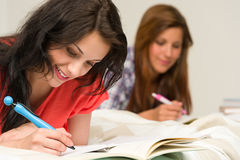 Young Teenager Girls Studying On Bed Stock Photo
