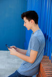 Young teenager with her cell phone. And a blue wall background Stock Photos