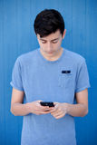 Young teenager with her cell phone. And a blue wall background Royalty Free Stock Photography
