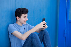 Young teenager with her cell phone. And a blue wall background Royalty Free Stock Images