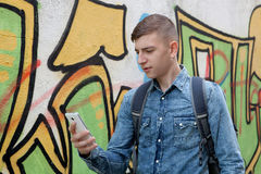 Young teenager with her cell phone. And near of a wall painted with graffiti Royalty Free Stock Photos