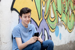 Young teenager with her cell phone. And a wall of background painted with graffiti Royalty Free Stock Photography
