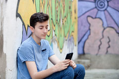 Young teenager with her cell phone. And a wall of background painted with graffiti Stock Photos