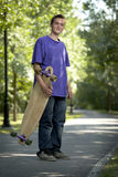 Young teenager holding his longboard Stock Photo