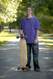 Young teenager holding his longboard Stock Photography