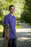 Young teenager holding his longboard Stock Image