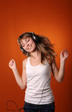 Young teenager listen to music. Pretty young teenager listen to music, isolated on orange Royalty Free Stock Photo