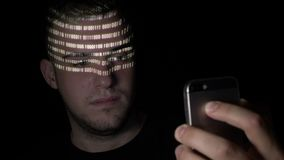 Young teenager male using a smartphone binary code application to scan his face and unlock it -. Young teenager male using a smartphone binary code application stock footage